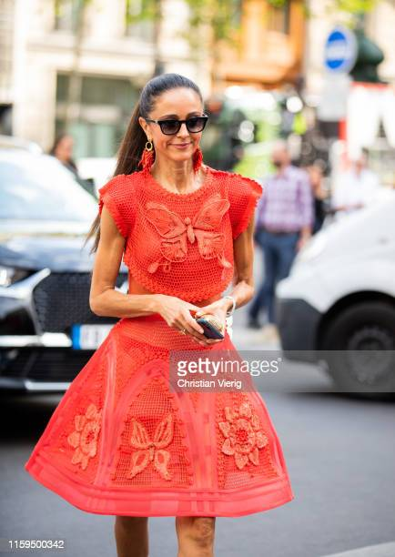A guest is seen wearing red dress outside Schiaparelli during Paris Fashion Week Haute Couture Fall/Winter 2019/2020 on July 01 2019 in Paris France