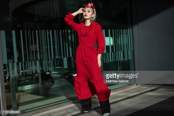 A guest is seen wearing red dress with floral hair piece during the Amazon Fashion Week TOKYO 2019 A/W on March 21 2019 in Tokyo Japan