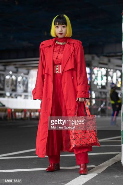 Guest is seen wearing red outfit with coat, dress, belt and Issey Miyake bag during the Amazon Fashion Week TOKYO 2019 A/W on March 19, 2019 in...