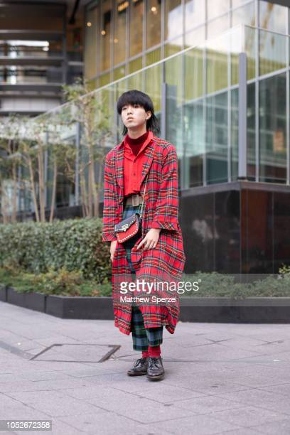 A guest is seen wearing red plaid coat green plaid pants red shirt and socks black leather shoes and bag during the Amazon Fashion Week TOKYO 2019...