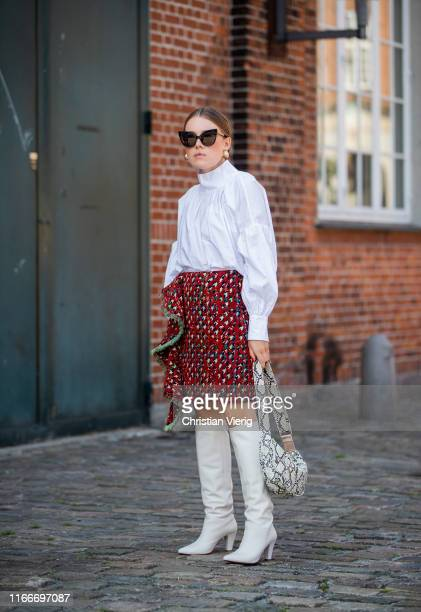 A guest is seen wearing red skirt white button shirt bag with snaker print boots outside Rodebjer during Copenhagen Fashion Week Spring/Summer 2020...