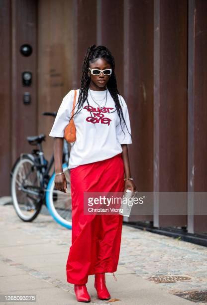 Guest is seen wearing red skirt, white shirt with print outside 7 days active during Copenhagen Fashion Week SS21 on August 10, 2020 in Copenhagen,...