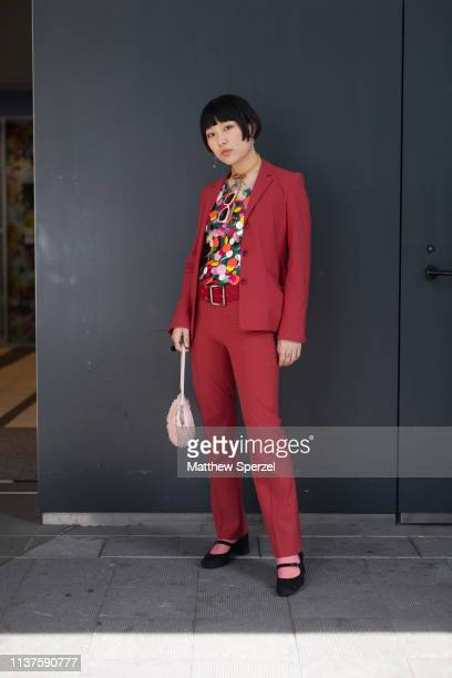 A guest is seen wearing red suit with colorful circle design shirt red belt pink bag during the Amazon Fashion Week TOKYO 2019 A/W on March 22 2019...
