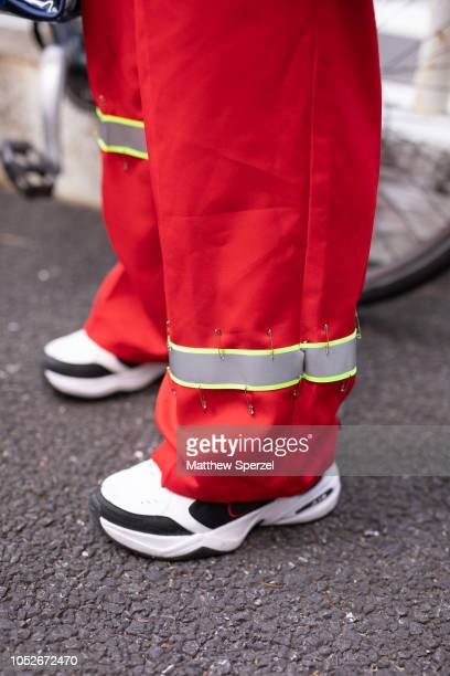 A guest is seen wearing red utility pants white/black sneakers navy coat and olive mesh vest during the Amazon Fashion Week TOKYO 2019 S/S on October...