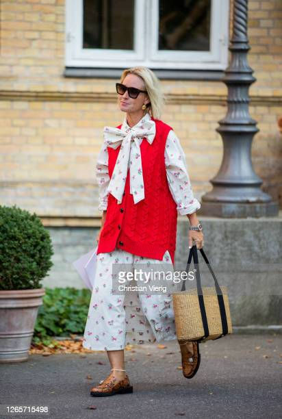 Guest is seen wearing red vest, dress with floral print outside By Malene Birger during Copenhagen Fashion Week Spring/Summer 2021 on August 12, 2020...