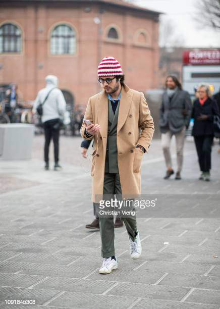 A guest is seen wearing red white striped beanie beige wool coat olive suit during the 95th Pitti Uomo at Fortezza Da Basso on January 09 2019 in...