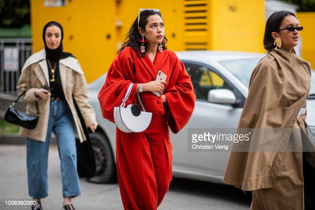 A guest is seen wearing red wrapped jacket wide leg pants white bag during MercedesBenz Tbilisi Fashion Week on November 3 2018 in Tbilisi Georgia