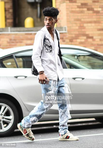 A guest is seen wearing ripped blue jeans and a white jacket outside the Death to Tennis show during New York Fashion Week Men's S/S 2018 at Skylight...