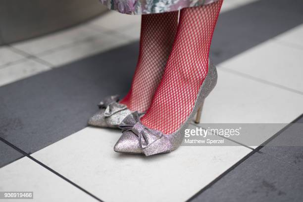 A guest is seen wearing silver bow shoes with red fishnets during the Amazon Fashion Week TOKYO 2018 A/W on March 22 2018 in Tokyo Japan