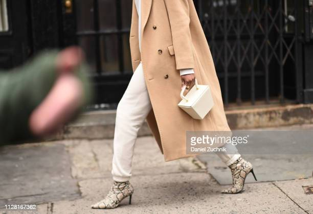 A guest is seen wearing snake skin heels and a white purse outside the Maryam Nassir Zadeh show during New York Fashion Week Women's Fall/Winter 2019...