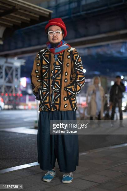 A guest is seen wearing southwestern pattern jacket blue/merlot scarf red beanie navy pants blue sneakers during the Amazon Fashion Week TOKYO 2019...