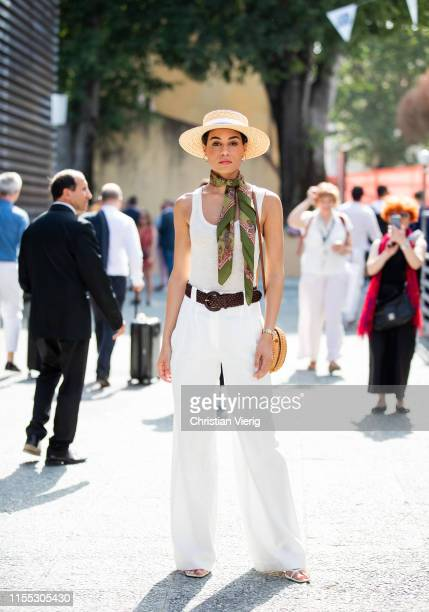 A guest is seen wearing staw hat white pants green scarf during Pitti Immagine Uomo 96 on June 11 2019 in Florence Italy