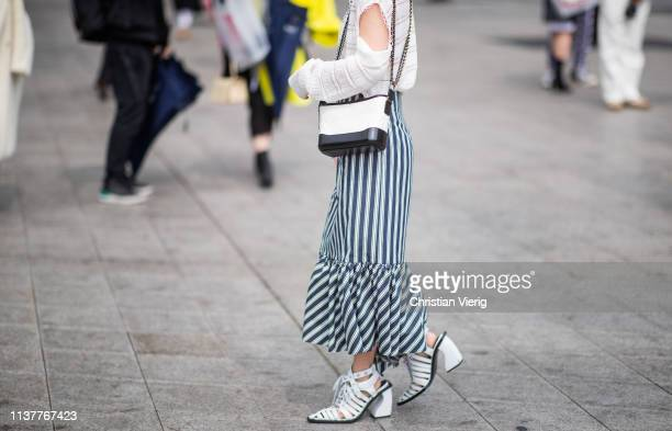 A guest is seen wearing striped aysmmetric skirt Chanel bag boots knit with slit at the Hera Seoul Fashion Week 2019 F/W at Dongdaemun Design Plaza...