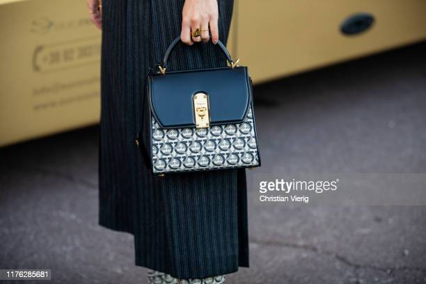Guest is seen wearing striped high waist skirt, bag, boots with print, hat outside the Ferragamo show during Milan Fashion Week Spring/Summer 2020 on...