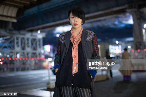 A guest is seen wearing striped pants navy/sea green/burgundy blazer peach scarf during the Amazon Fashion Week TOKYO 2019 A/W on March 23 2019 in...