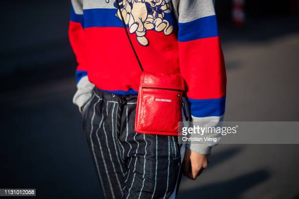 A guest is seen wearing striped pants red Balenciaga bag outside Gucci on Day 1 Milan Fashion Week Autumn/Winter 2019/20 on February 20 2019 in Milan...