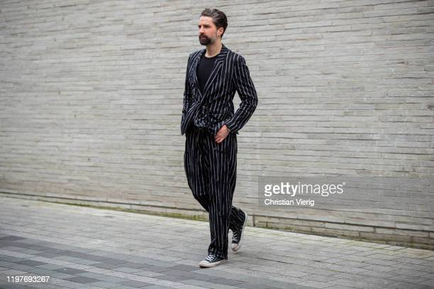 A guest is seen wearing stripped suit outside Chalayan during London Fashion Week Men's January 2020 on January 05 2020 in London England