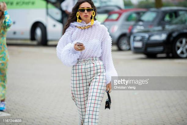 Guest is seen wearing sunglasses, plaid pants outside Munthe during Copenhagen Fashion Week Spring/Summer 2020 on August 07, 2019 in Copenhagen,...