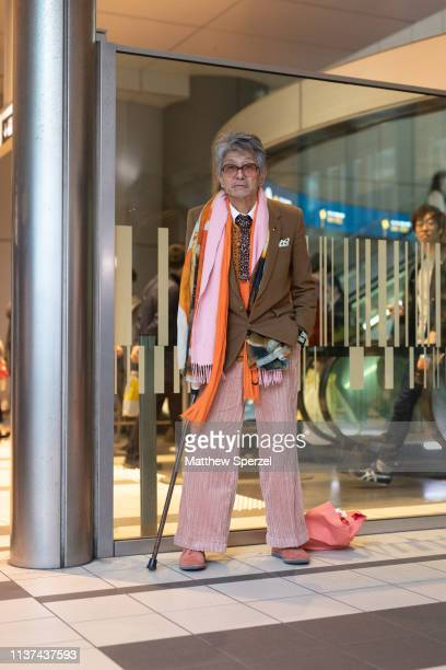 A guest is seen wearing tan blazer pink/orange scarf shirt and tie during the Amazon Fashion Week TOKYO 2019 A/W on March 21 2019 in Tokyo Japan