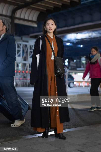 A guest is seen wearing tan dress black coat and bag during the Amazon Fashion Week TOKYO 2019 A/W on March 23 2019 in Tokyo Japan