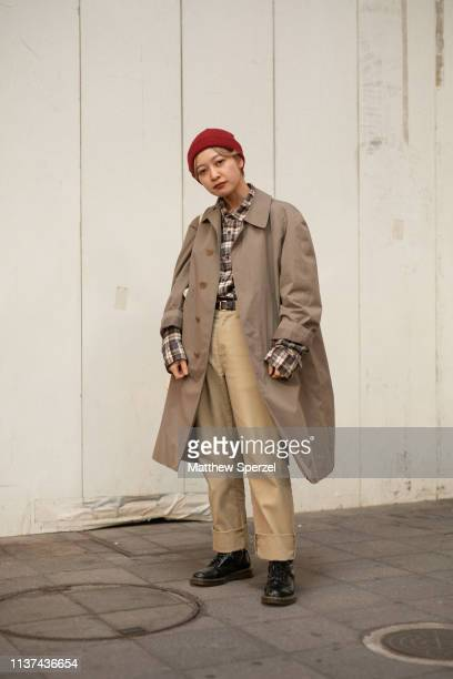 A guest is seen wearing taupe coat oversized plaid shirt red beanie khaki pants during the Amazon Fashion Week TOKYO 2019 A/W on March 21 2019 in...