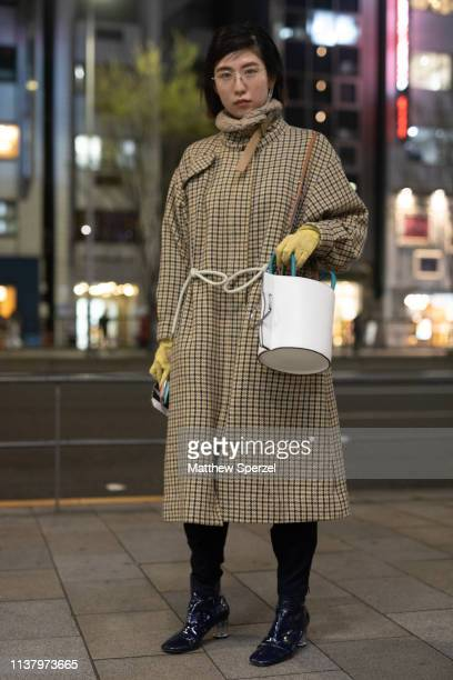 A guest is seen wearing taupe pattern coat white bucket bag during the Amazon Fashion Week TOKYO 2019 A/W on March 23 2019 in Tokyo Japan