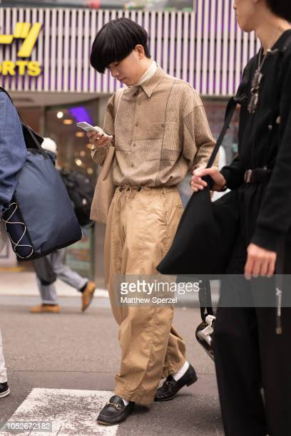 A guest is seen wearing taupe shirt tan pants and black loafers during the Amazon Fashion Week TOKYO 2019 S/S on October 20 2018 in Tokyo Japan