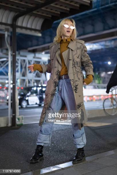 A guest is seen wearing taupe with hand drawn graphics coat copper sweater blue jeans during the Amazon Fashion Week TOKYO 2019 A/W on March 23 2019...