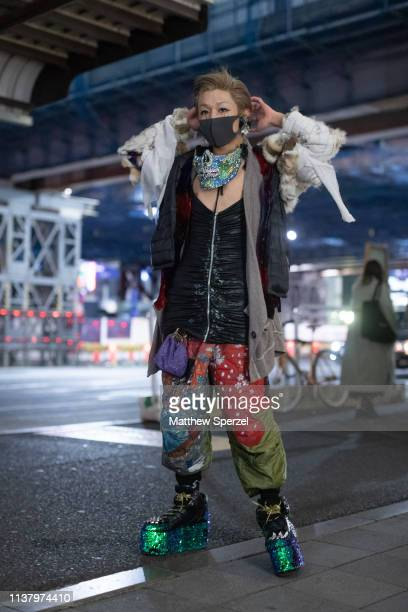 A guest is seen wearing teal custom face mask black top patchwork pants green glitter platforms during the Amazon Fashion Week TOKYO 2019 A/W on...