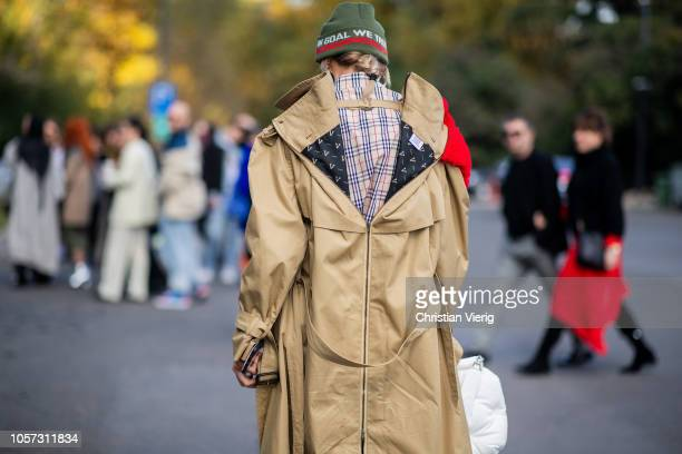 A guest is seen wearing trench coat beanie pants with snake print white sneakers white bag during MercedesBenz Tbilisi Fashion Week on November 4...