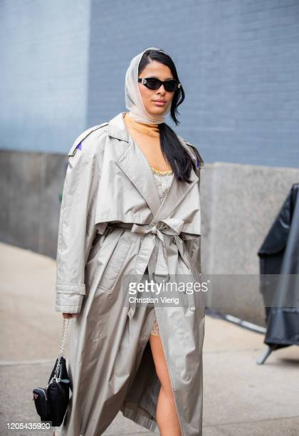 Guest is seen wearing trench coat, head scarf, Prada bag outside Jonathan Simkhai during New York Fashion Week Fall / Winter on February 10, 2020 in...