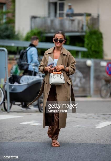 Guest is seen wearing trench coat outside outside Day Birger et Mikkelsen on August 09, 2021 in Copenhagen, Denmark.