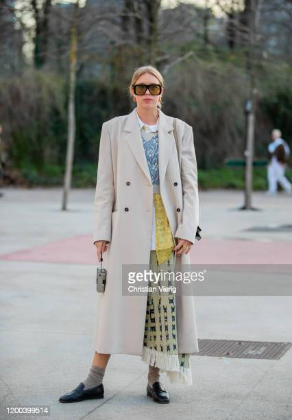 A guest is seen wearing trench coat sheer top yellow skirt with print outside Jacquemus during Paris Fashion Week Menswear F/W 20202021 on January 18...