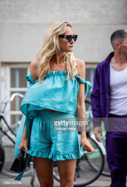 Guest is seen wearing turquoise blouse and shorts outside Selected during Copenhagen Fashion Week Spring/Summer 2021 on August 12, 2020 in...