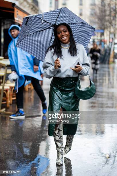 Guest is seen wearing turquoise turtleneck, green skirt with slit, bag, boots with snake print outside Sacai during Paris Fashion Week - Womenswear...