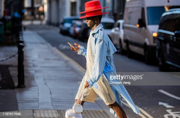 A guest is seen wearing two red hats blue coat outside Edward Crutchley during London Fashion Week Men's January 2020 on January 04 2020 in London...