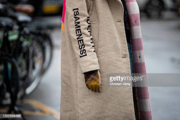A guest is seen wearing two tone pink white checkered Muf 10 coat gloves denim jeans outside Carcel on Day 1 during Copenhagen Fashion Week...