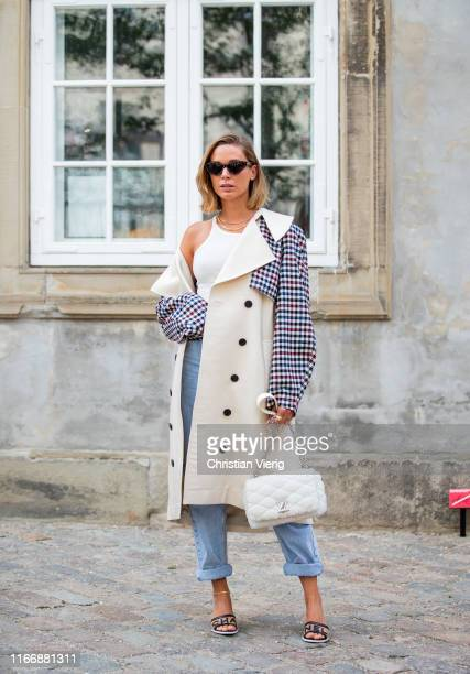 Guest is seen wearing two trench coat, Louis Vuitton bag, denim jeans outside Designers Remix during Copenhagen Fashion Week Spring/Summer 2020 on...
