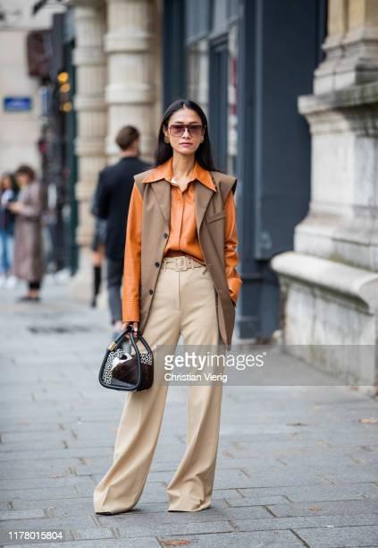 Guest is seen wearing vest, orange brown button shirt, beige pants during Paris Fashion Week Womenswear Spring Summer 2020 on September 29, 2019 in...