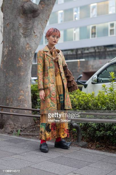 A guest is seen wearing vintage pattern coat and dress with black shoes and brown fringe bag during the Amazon Fashion Week TOKYO 2019 A/W on March...