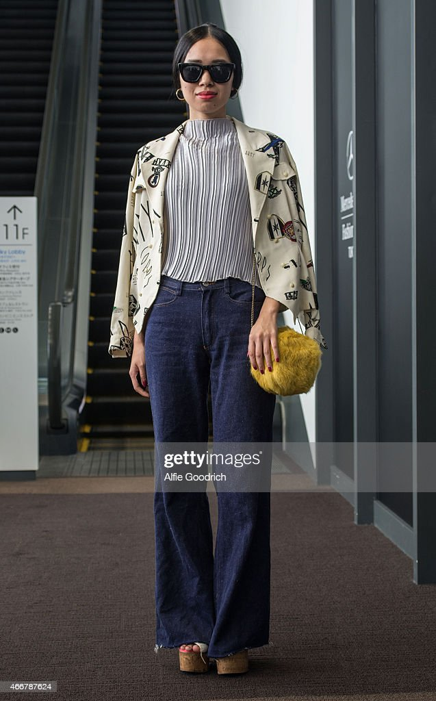 A guest is seen wearing vintage shirt and jeans and thrift-store yellow clutch handbag during the Mercedes Benz Fashion Week TOKYO 2015 A/W at Shibuya Hikarie on March 19, 2015 in Tokyo, Japan.