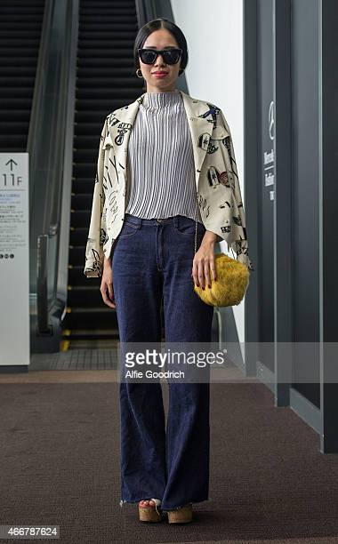 A guest is seen wearing vintage shirt and jeans and thriftstore yellow clutch handbag during the Mercedes Benz Fashion Week TOKYO 2015 A/W at Shibuya...