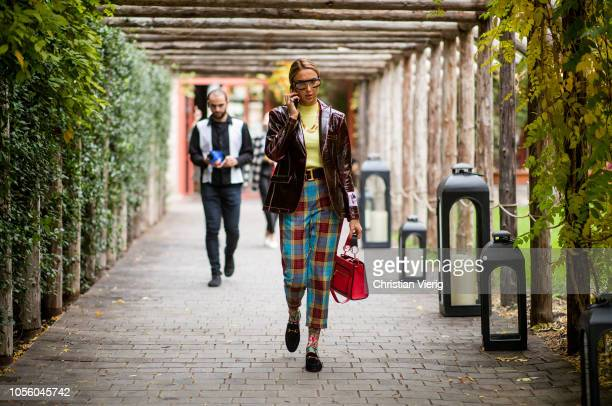 A guest is seen wearing vinyl jacket plaid pants Gucci shoes socks with print red bag sunglasses during MercedesBenz Tbilisi Fashion Week on November...
