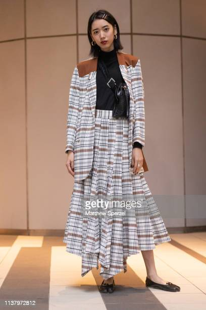A guest is seen wearing white and brown patten blazer and skirt black turtleneck black crossbody bag and tabi flats during the Amazon Fashion Week...