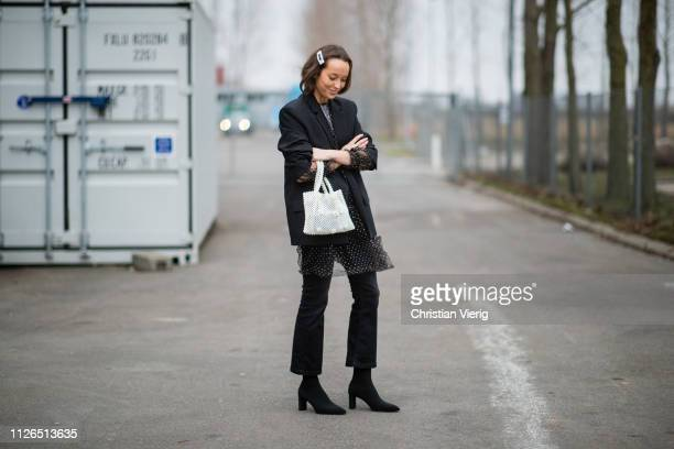 A guest is seen wearing white bag sheer dress cropped denim jeans black boots outside Munthe during the Copenhagen Fashion Week Autumn/Winter 2019...