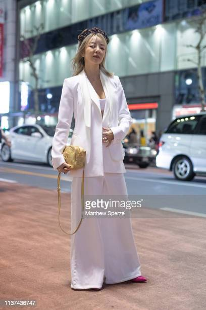 A guest is seen wearing white blazer and pants with yellow bag and headband during the Amazon Fashion Week TOKYO 2019 A/W on March 21 2019 in Tokyo...