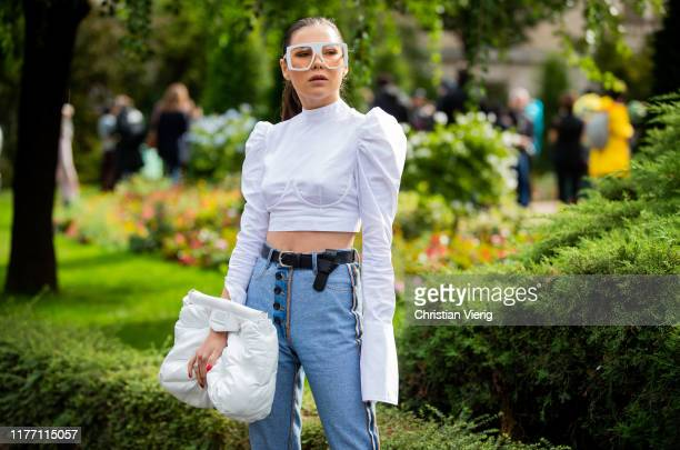 Guest is seen wearing white blouse, denim jeans, Margiela bag outside Maison Margiela Show during Paris Fashion Week Womenswear Spring Summer 2020 on...