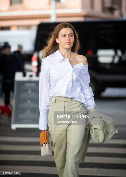 A guest is seen wearing white blouse olive cropped pants outside Tory Burch during New York Fashion Week Autumn Winter 2019 on February 10 2019 in...