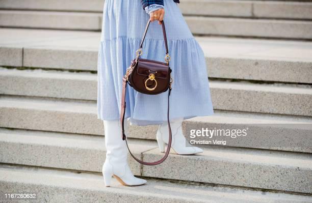 Guest is seen wearing white boots, Chloe bag outside Samsøe & Samsøe during Copenhagen Fashion Week Spring/Summer 2020 on August 07, 2019 in...