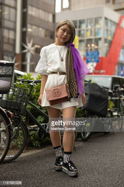 A guest is seen wearing white dress brown belt Tory Burch brown bag purple and Fendi scarves black creepers during the Amazon Fashion Week TOKYO 2019...
